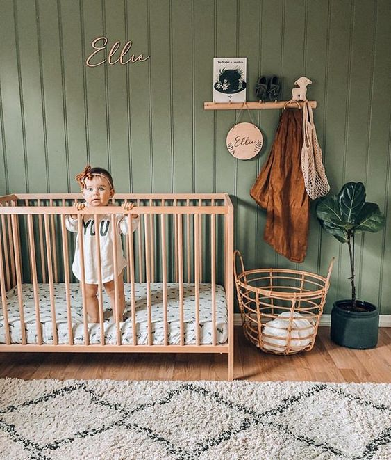 a cozy and simple nursery with a grene beadboard accent wall, light stained furniture, a statement potted plant and some printed textiles