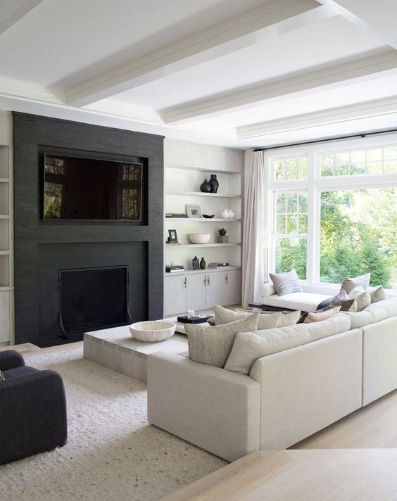 a cozy black and white contemporary living room with a built-in TV and fireplace, open shelves, a cabinet, a neutral sofa and daybed, a low table and a black chair