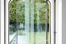 a delicate and catchy arched glass pivot door that leads to the garden is a lovely idea for an elegant home