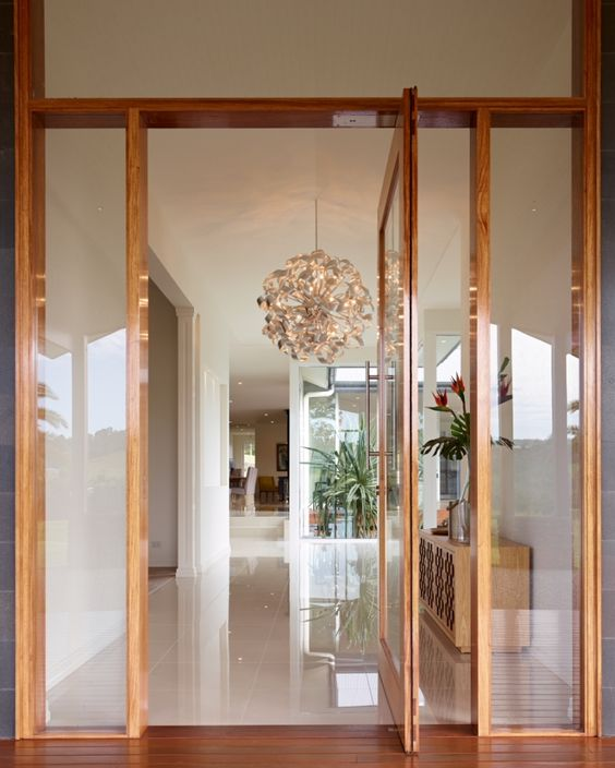 a delicate rich-stained and glass pivot entrance door will create a subtle and lightweight look at the entrance and will welcome