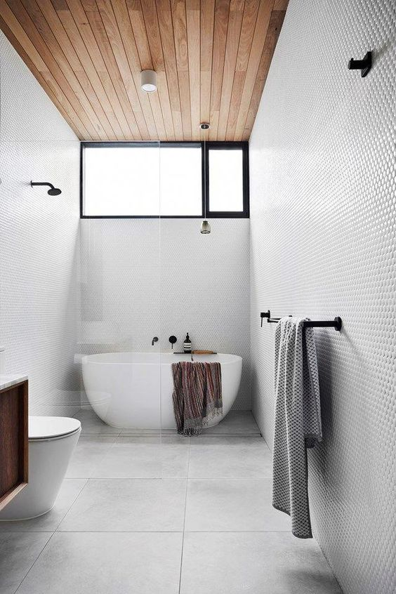 a dove grey bathroom with penny and large scale tiles, a wooden ceiling, an oval tub and black fixtures is very stylish