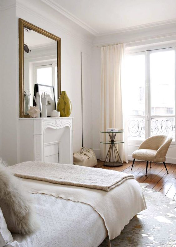 a dreamy Parisian style bedroom with a non working fireplace, a cool chair and a round table, a large mirror in a gilded frame and neutral textiles