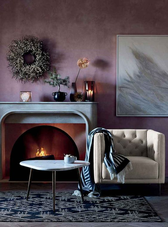 a dreamy living room with a pale purple accent wall, a fireplace with a stone mantel, a creamy chair, a printed rug and some lovely decor