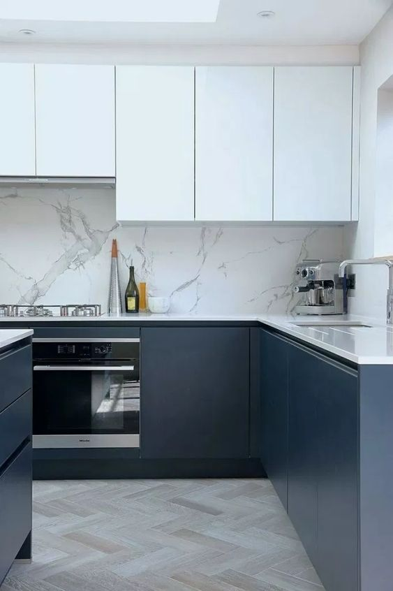 a fab contemporary kitchen with sleek white and navy cabinets, a white stone backsplash and countertops and a skylight