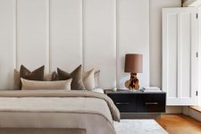 a fabulous contemporary bedroom with a headboard clad with upholstered panels, a bed with neutral earthy bedding and a matching bench, a large nightstand with a lamp