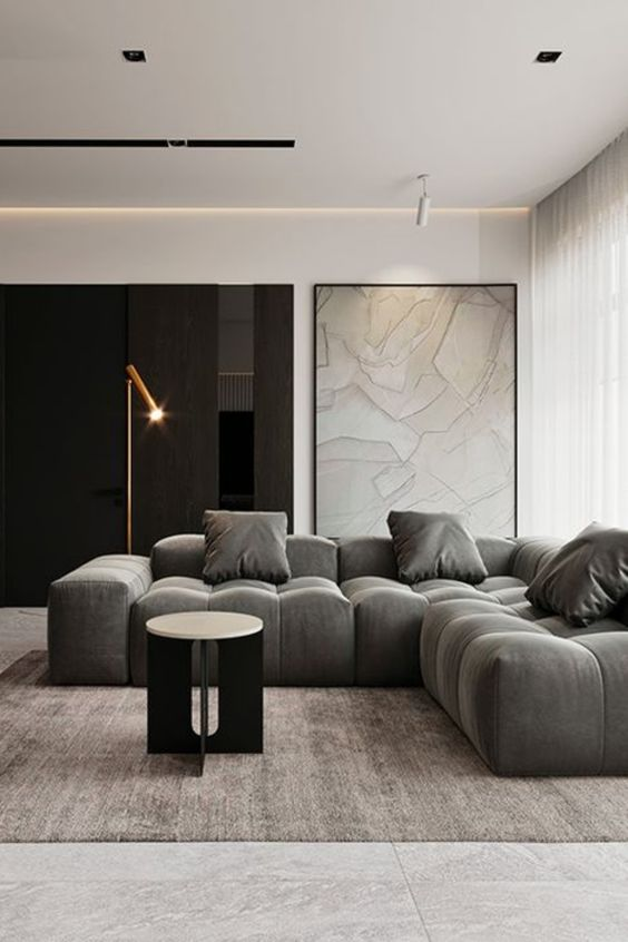 a fabulous contemporary living room in a monochromatic color palette, a lovely low sectional, a round table, a floor lamp and a map in a frame