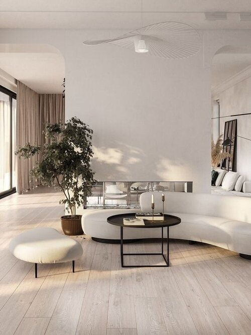 a fabulous contemporary living room with a built-in fireplace, a curved sofa and a footrest, a black coffee table, potted plants