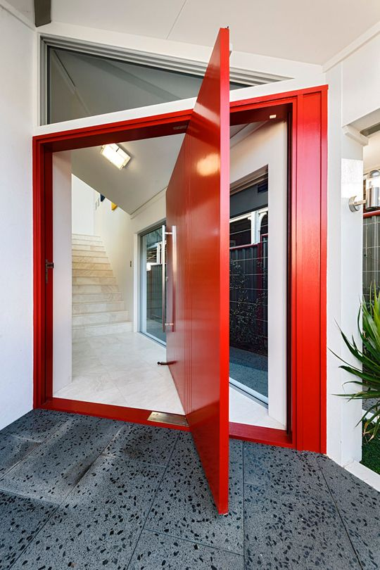 a fantastic red pivot door with a large handle is a gorgeous color statement and its design adds even more interest to the space