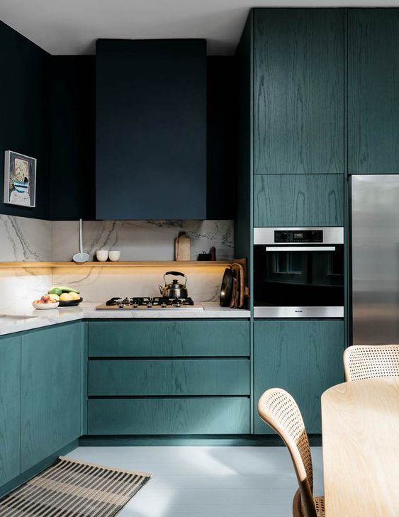 a fantastic teal kitchen that shows off grains of wood, a navy hood that merges with the wall, a white stone backsplash and countertop