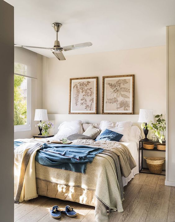 a farmhouse light-filled bedroom with an upholstered white bed and open nightstands, baskets, potted greenery and botanical artworks