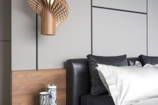 a gorgeous contemporary bedroom with a grey panel accent wall, a black leather bed, contrasting bedding, a floating nightstand and a jaw-dropping pendant lamp