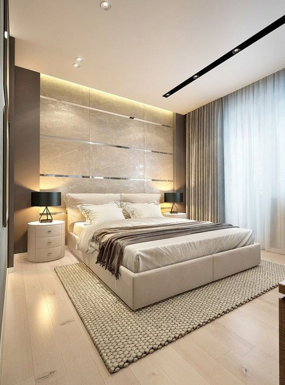 a gorgeous contemporary bedroom with a tile and metallic line accent wall, a neutral upholstered bed, round white nightstands, black lamps and several layers of light