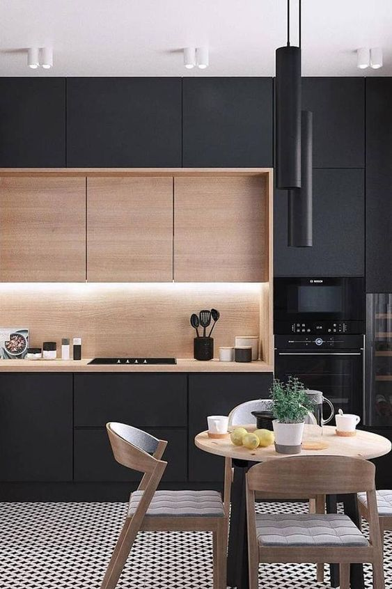 a gorgeous contemporary kitchen with sleek black cabinets, a row of light stained ones, built-in lights and black tube pendant lamps over the dining space