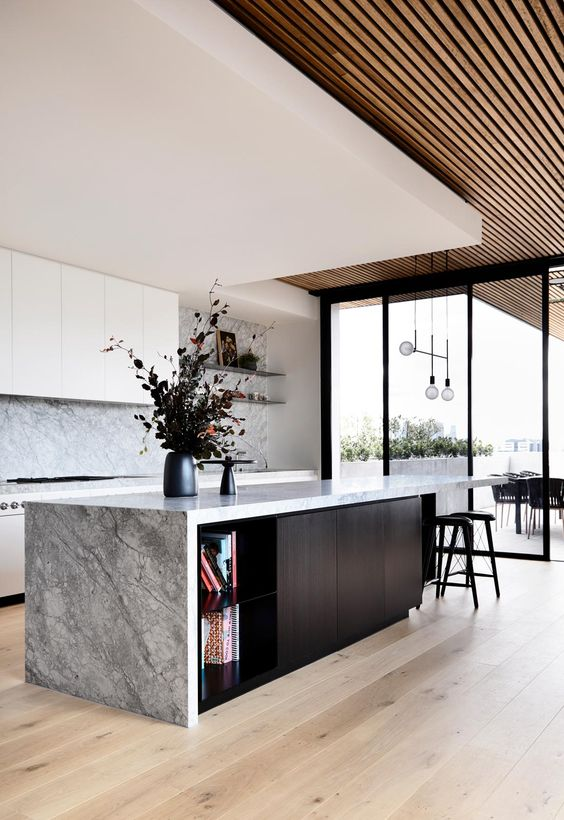 a gorgeous contemporary ktichen with sleek white cabinets, a grey stone backsplash and countertops, a black kitchen island and a layered ceiling