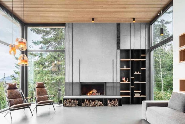 a gorgeous contemporary living room with a view, a built-in fireplace and firewood storage, a grey sofa, leather chairs, pendant lamps