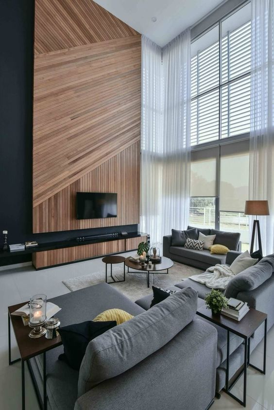 a gorgeous contemporary living room with a wood clad accent wall, a TV, grey furniture, side and coffee tables and double-height windows