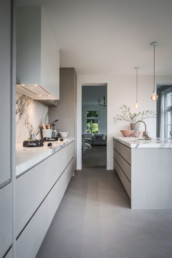 a heavenly grey contemporary kitchen with sleek cabinets and a large kitchen island, a white stone backsplash and countertops and pendant lamps