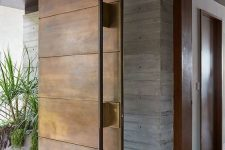 a heavy aged metal pivot door with a large handle is a bold idea for a contemporary space and can be rocked in any modern entrance