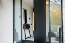 a heavy black metal pivot door with a long light-stained handle is a cool idea for making and statement with style