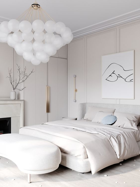 a jaw-dropping contemporary bedroom in neutrals, with an upholstered bed and a curved bench, a fireplace and a fantastic bubble chandelier