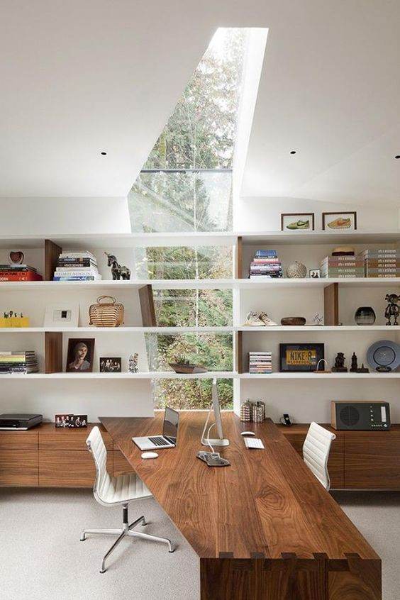 a jaw-dropping contemporary home office with a window skylight, open shelves with books and decor, storage units and a built-in desk, the shape of which echoes with the skylight