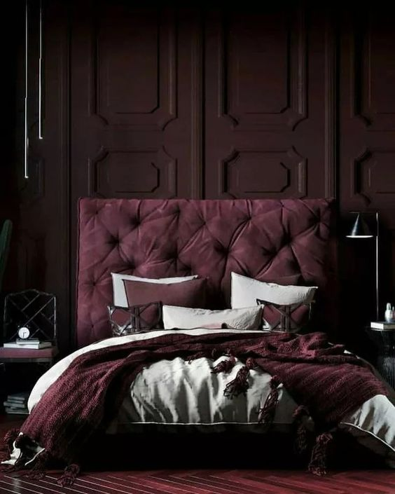 a jaw-dropping moody bedroom with a deep purple paneled wall, a purple upholstered bed, mismatching nightstands and purple and white bedding