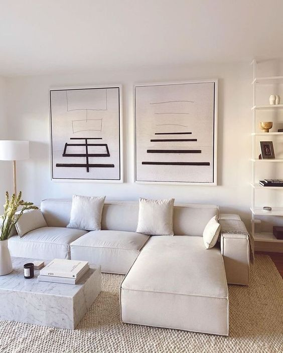 a laconic contemporary living room in neutrals, with a low sectional, a marble coffee table, an open shelving unit, a graphic gallery wall