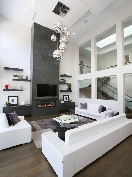 a laconic contemporary living room with a fireplace clad with tiles, white sofas and a chair, a tiered glass coffee table and open shelves