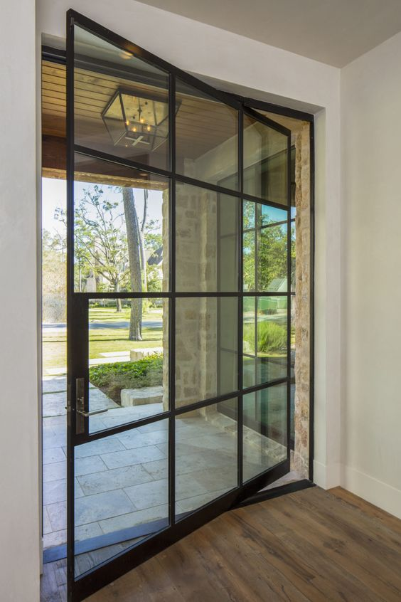 a large French pivot door like this one looks extremely elegant and chic and makes the entrace look very lightweight