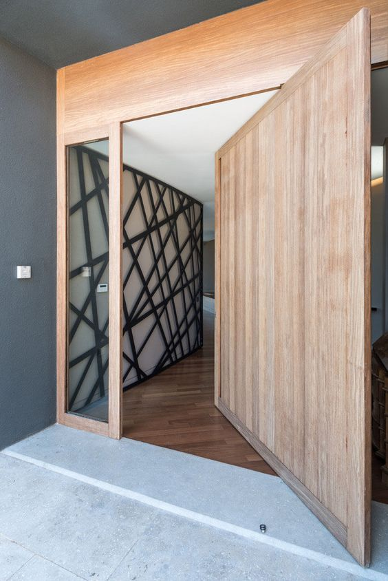 a large light-stained wood pivot door with glass panes and no handles or knobs is a very cool idea for a minimalist entrance