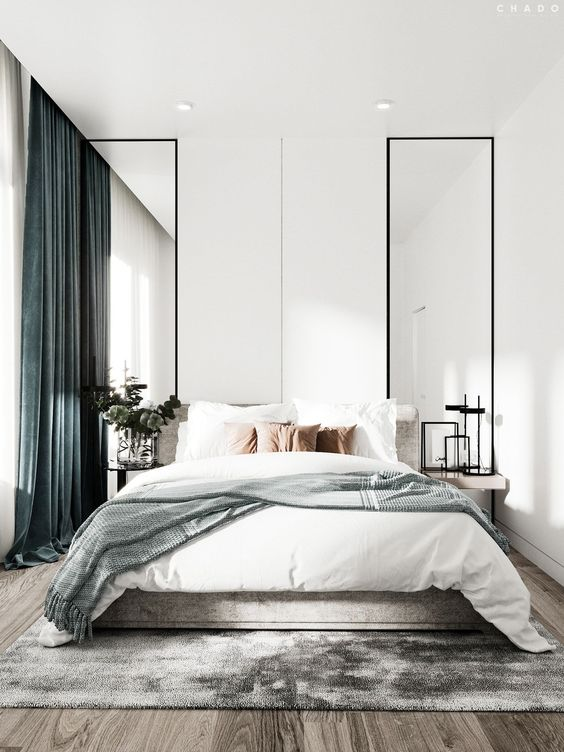 a light-filled contemporary bedroom with tall mirrors, floating nightstands, a bed with neutral bedding and green curtains is pure chic
