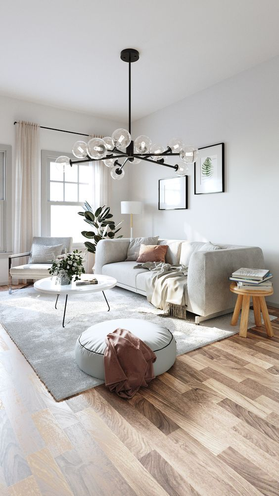 a light-filled contemporary living room with a comfy sofa, a matching chair, a round table, a wooden stool, a pouf and some artworks