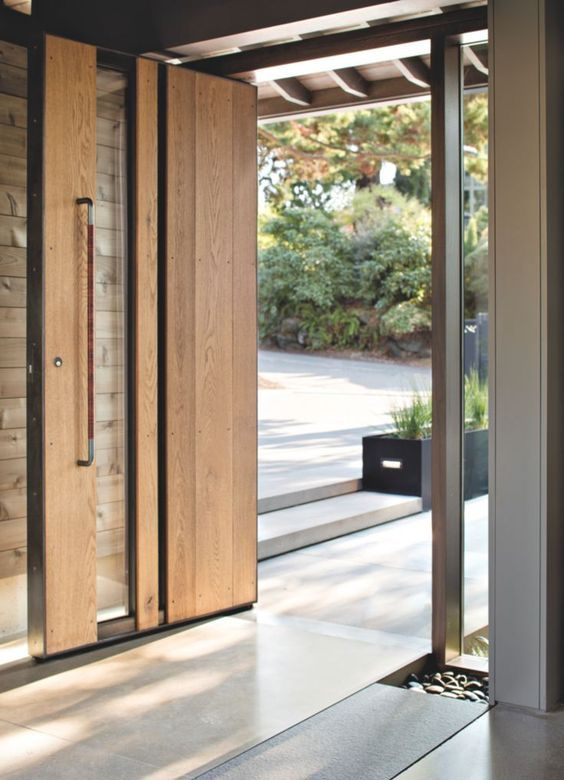 a light-stained and glass pivot door with a handle is a lovely idea for a modern space, it makes the entrance cool