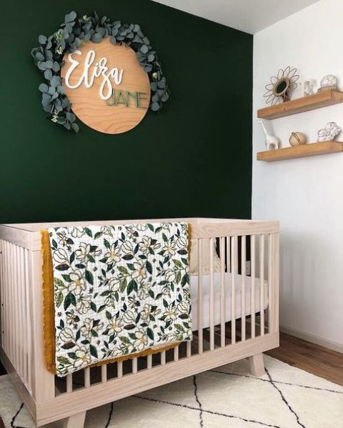 a little and lovely nursery with a dark green accent wall, a stained crib, open shelves and a cool decoration of wood and eucalyptus