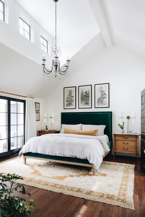 a lovely bedroom with a double height ceiling, a vintage chandelier that highlights it, a green upholstered bed, a grid gallery wal and stained nightstands