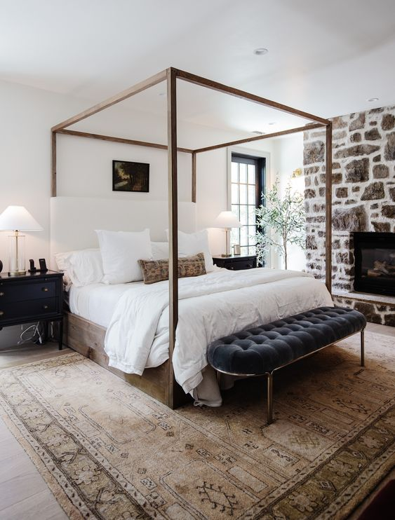 a lovely bedroom with a farmhouse feel, a stone clad fireplace, a canopy bed, an upholstered bench, black nightstands, neutral bedding and a potted tree