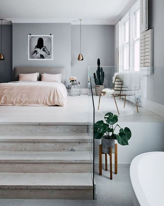 a lovely bedroom with a grey accent wall, a grey upholstered bed, pink bedding, pendant lamps, a potted cactus and a statement artwork