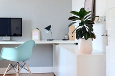 a lovely contemporary home office with a sleek storage unit and a built-in desk, a mint blue chair, potted greenery and a cool clock