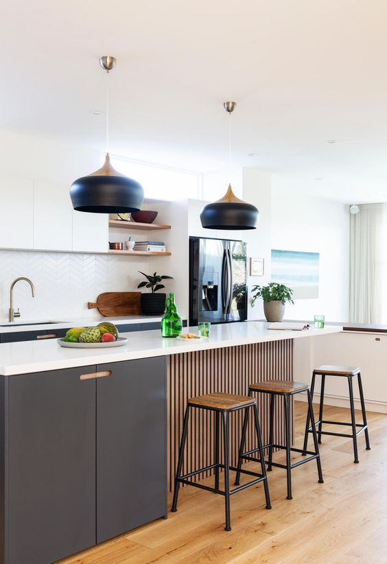 a lovely contemporary kitchen with graphite grey and white cabinets, a white chevron tile backsplash, catch black pendant lamps