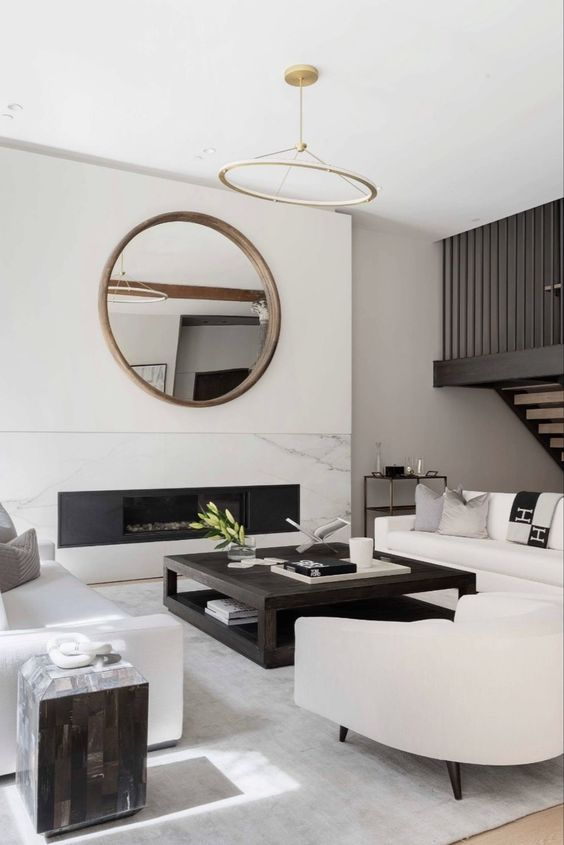 a lovely contemporary living room with a built-in fireplace, a round mirror, white sofas and a chair, a low coffee table and a side table