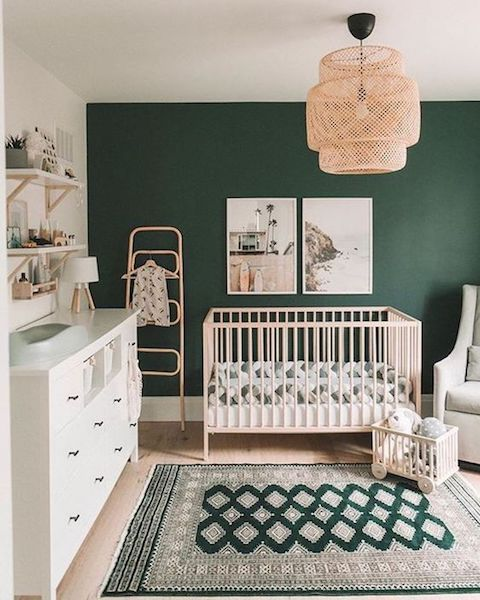 a lovely gender neutral nursery with a dark green accent wall, neutral furniture, a woven pendant lamp, some open shelves and printed bedding