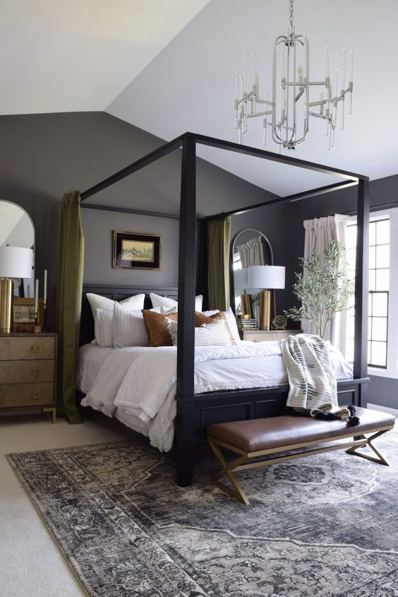 a lovely master bedroom with grey walls, a black canopy bed, neutral bedding, green curtains, a modern chandelier and a leather bench