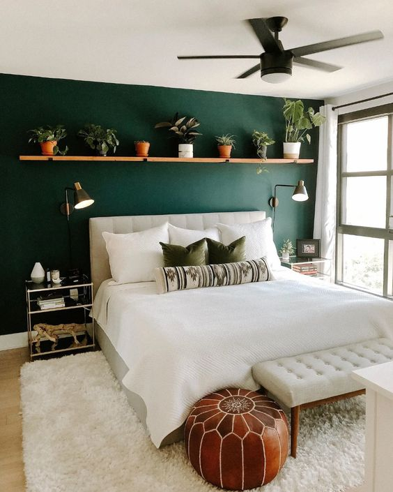 a lovely mid-century modern bedroom with a green accent wall, a creamy upholstered bed and a bench, a shelf with potted greenery