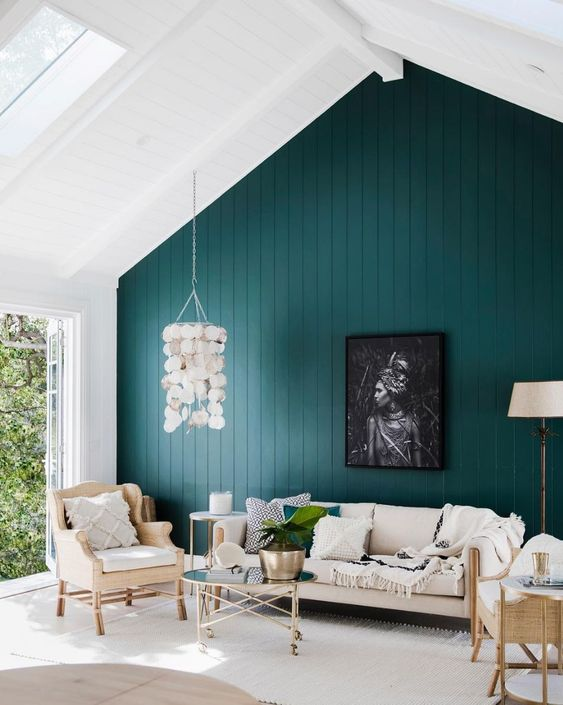 a lovely modern attic living room with a dark green accent wall, neutral funiture, a seashell pendant lamp and printed textiles