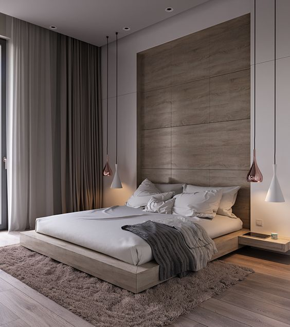a luxurious contemporary bedroom done in warm neutrals, with a wood clad niche and a matching bed, neutral textiles and cool pendant lamps
