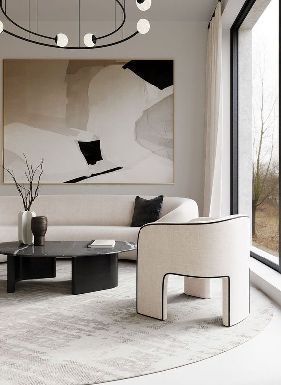 a luxurious contemporary living room in neutrals and black, with a curved sofa and a chair on three legs, a black marble table, a chandelier plus a statement artwork