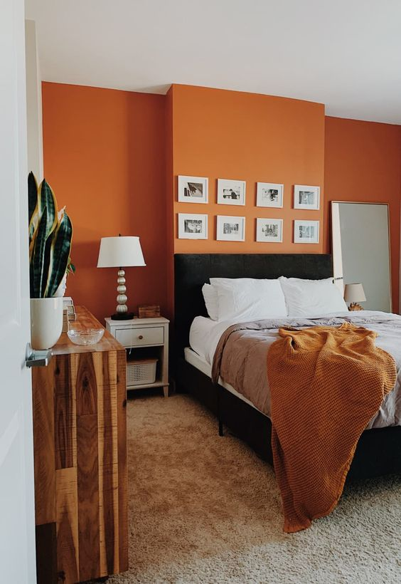 a mid-century modern bedroom with an orange accent wall, a black bed and neutral nightstands, a reclaimed wood dresser and a small gallery wall