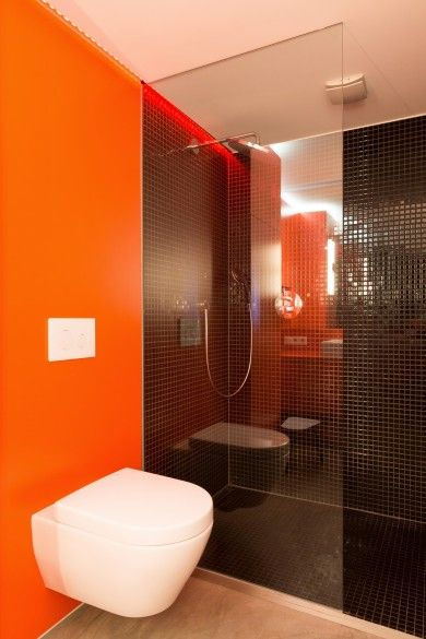 a minimalist bathroom with an orange accent wall, a shower space clad with black tiles is a very chic and cool space