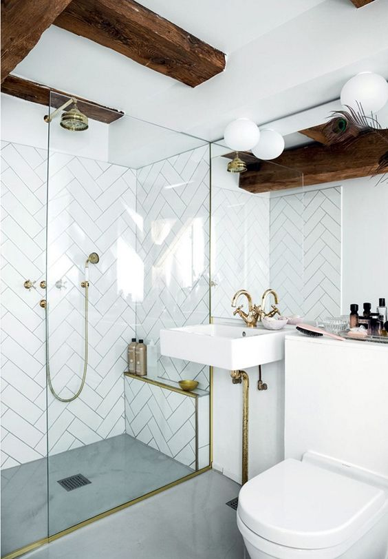 a modern bathroom with white chevron tiles, dark stained beams, white appliances and gold fixtures and large scale tiles on the floor