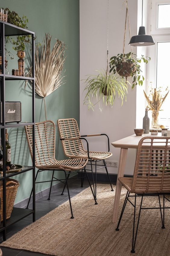 a modern boho dining space with a green accent wall, a light stained table and rattan chairs, a black shelvint unit and potted greenery